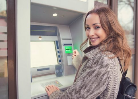 Young happy woman with credit card using ATM